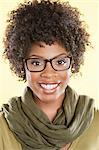Portrait of a happy African American woman wearing glasses with a stole round her neck over colored background Stock Photo - Premium Royalty-Free, Artist: ableimages, Code: 693-06324604