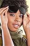 Portrait of an African American woman holding sunglasses with a stole round her neck over colored background Stock Photo - Premium Royalty-Free, Artist: ableimages, Code: 693-06324611