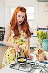 Portrait of a redheaded woman preparing omelet Stock Photo - Premium Royalty-Free, Artist: Cultura RM, Code: 693-06324757