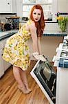 Full length portrait of a young woman standing by an open oven Stock Photo - Premium Royalty-Free, Artist: Blend Images, Code: 693-06324763