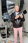 Front view of senior man with camera in photographer's studio Stock Photo - Premium Royalty-Free, Artist: AWL Images, Code: 693-06324865