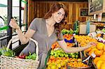 Portrait of a happy young female shopping for fruits in market Stock Photo - Premium Royalty-Free, Artist: Ikon Images, Code: 693-06324907