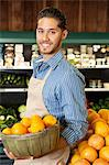 Happy salesperson with basket full of oranges in market Stock Photo - Premium Royalty-Free, Artist: CulturaRM, Code: 693-06324937