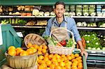 Portrait of man in supermarket with vegetable basket standing near oranges stall Stock Photo - Premium Royalty-Free, Artist: Aflo Relax, Code: 693-06324949