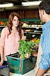 Beautiful young woman looking at store clerk in supermarket Stock Photo - Premium Royalty-Free, Artist: ableimages, Code: 693-06324953