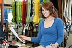 Portrait of beautiful young woman with paper and textile samples standing in store Stock Photo - Premium Royalty-Free, Artist: Cultura RM, Code: 693-06325081