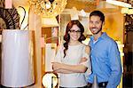 Portrait of a happy couple standing together in lights store Stock Photo - Premium Royalty-Free, Artist: Blend Images, Code: 693-06325141