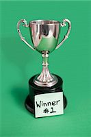Trophy with sticky note for winner over colored background Stock Photo - Premium Royalty-Freenull, Code: 693-06325254