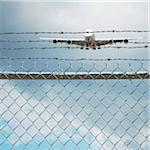 Jumbo Jet and Chain Link Fence with Barbed Wire, Pearson International Airport, Toronto, Ontario, Canada Stock Photo - Premium Royalty-Free, Artist: Andrew Kolb, Code: 600-06325428