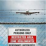 Jumbo Jet and Restricted Area Sign on Chain Link Fence with Barbed Wire, Pearson International Airport, Toronto, Ontario, Canada Stock Photo - Premium Royalty-Free, Artist: Andrew Kolb, Code: 600-06325429