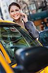 A happy young woman talking on her mobile cell phone by a yellow taxi cab. Shot on location in New York City Stock Photo - Royalty-Free, Artist: darrenbaker                   , Code: 400-06332106