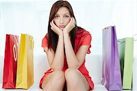 Portrait of young stressed brunette surrounded by paperbags Stock Photo - Royalty-Freenull, Code: 400-06332983