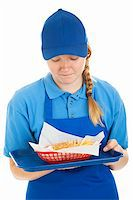 Teenage fast food worker disgusted by the burger and fries she's serving.  Isolated on white. Stock Photo - Royalty-Freenull, Code: 400-06333293