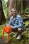 Man with Canteen Crouching in Forest Stock Photo - Premium Rights-Managed, Artist: Ty Milford, Code: 700-06334620
