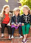 Three smiling girls sitting on a brick wall. Stock Photo - Premium Royalty-Freenull, Code: 6106-06335919