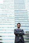 Businessman with arms crossed in front of glass building