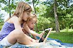 Two girls sitting on picnic blanket with digital tablet Stock Photo - Premium Royalty-Free, Artist: CulturaRM, Code: 614-06336320