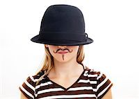 Portrait of girl wearing hat with fake moustache, studio shot Stock Photo - Premium Royalty-Freenull, Code: 6102-06336546