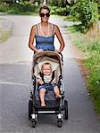 Smiling woman walking with son in pram Stock Photo - Premium Royalty-Free, Artist: Siephoto, Code: 6102-06336696