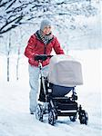 Smiling mother walking with pram at winter landscape Stock Photo - Premium Royalty-Free, Artist: Siephoto, Code: 6102-06336699