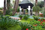 An ornately tiled pavilion surrounded by geraniums and palm trees in the garden of La Mamounia Hotel in Marrakech, Morocco, North Africa, Africa