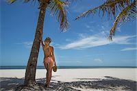 Woman holding tropical fruit on beach Stock Photo - Premium Royalty-Freenull, Code: 649-06352426