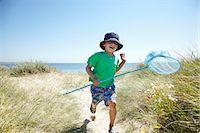 Boy carrying fishing net on beach Stock Photo - Premium Royalty-Freenull, Code: 649-06352470