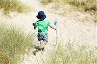 Boy carrying fishing net on beach Stock Photo - Premium Royalty-Freenull, Code: 649-06352471