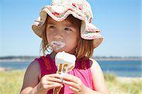 Girl eating ice cream on beach Stock Photo - Premium Royalty-Freenull, Code: 649-06352474