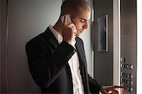Businessman on cell phone in elevator Stock Photo - Premium Royalty-Freenull, Code: 649-06352491