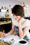 Smiling woman writing in cafe Stock Photo - Premium Royalty-Free, Artist: Westend61, Code: 649-06352537