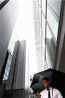 Businessman walking under umbrella Stock Photo - Premium Royalty-Freenull, Code: 649-06352706