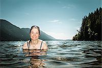 Woman standing in still lake Stock Photo - Premium Royalty-Freenull, Code: 649-06352774