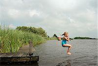 Girl jumping into rural lake Stock Photo - Premium Royalty-Freenull, Code: 649-06352994