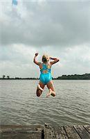 Girl jumping into rural lake Stock Photo - Premium Royalty-Freenull, Code: 649-06352995