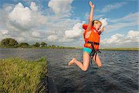 Girl jumping into rural lake Stock Photo - Premium Royalty-Freenull, Code: 649-06352998