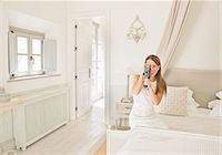 rich lifestyle - Woman using video camera in bedroom Stock Photo - Premium Royalty-Freenull, Code: 649-06353236