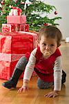 Baby girl crouching in front of Christmas presents Stock Photo - Premium Royalty-Free, Artist: Albert Normandin, Code: 632-06353945