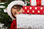Boy peeking around stack of Christmas presents Stock Photo - Premium Royalty-Freenull, Code: 632-06354292