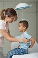 Mother helping little boy on examination table Stock Photo - Premium Royalty-Freenull, Code: 632-06354402