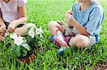 Children sitting on grass with potted flowers, cropped Stock Photo - Premium Royalty-Free, Artist: Uwe Umsttter, Code: 633-06354707