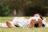 Children lying together under blanket on grass Stock Photo - Premium Royalty-Freenull, Code: 633-06354715