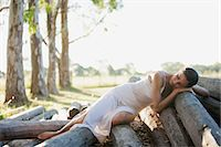 Woman reclining on pile of logs Stock Photo - Premium Royalty-Freenull, Code: 633-06354962