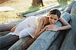 Woman reclining on pile of logs Stock Photo - Premium Royalty-Freenull, Code: 633-06355079