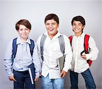 Three happy schoolboys isolated on gray&white background, back to school, best friends classmates, smiling cheerful teenagers with backpacks and books, knowledge and education concept   Stock Photo - Royalty-Freenull, Code: 400-06362511