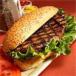 Grilled Steak Sandwich on a Sesame Seed Bun with Lettuce Stock Photo - Premium Royalty-Freenull, Code: 659-06373059