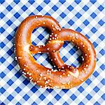 A pretzel on a blue and white tablecloth Stock Photo - Premium Royalty-Freenull, Code: 659-06373074