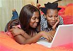 Two women lying on a bed using a laptop, Gugulethu, Cape Town Stock Photo - Premium Royalty-Free, Artist: Martin Ruegner, Code: 682-06374089