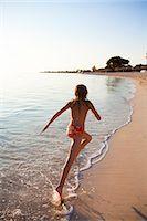 Girl running on beach Stock Photo - Premium Royalty-Freenull, Code: 6102-06374487