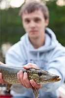 fishing - Young man showing his catch Stock Photo - Premium Royalty-Freenull, Code: 698-06374612